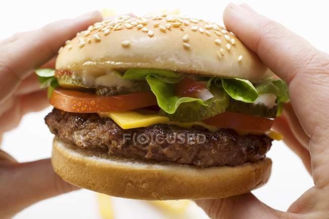 Руки держат чизбургер — стоковое фото