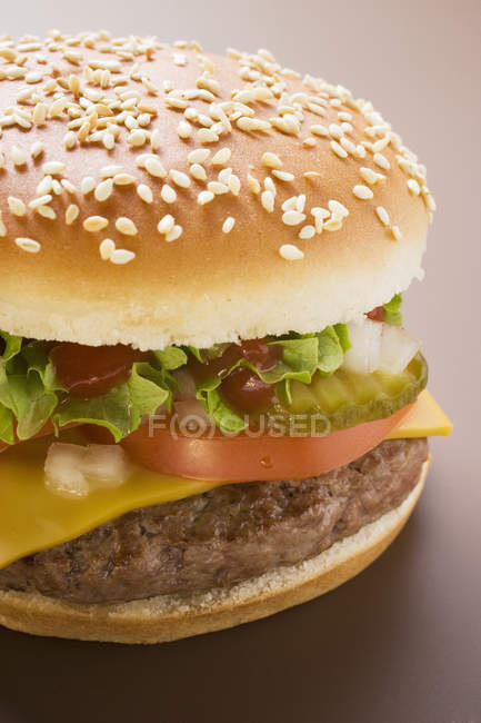 Cheeseburger con tomate y pepinillos - foto de stock