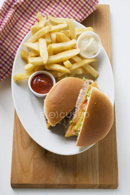 Coupées en deux cheeseburger avec frites — Photo de stock