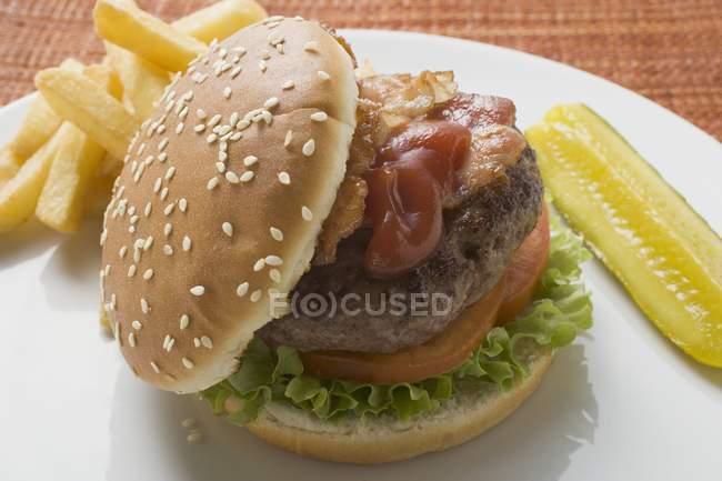 Hamburguesa con tocino y patatas fritas - foto de stock
