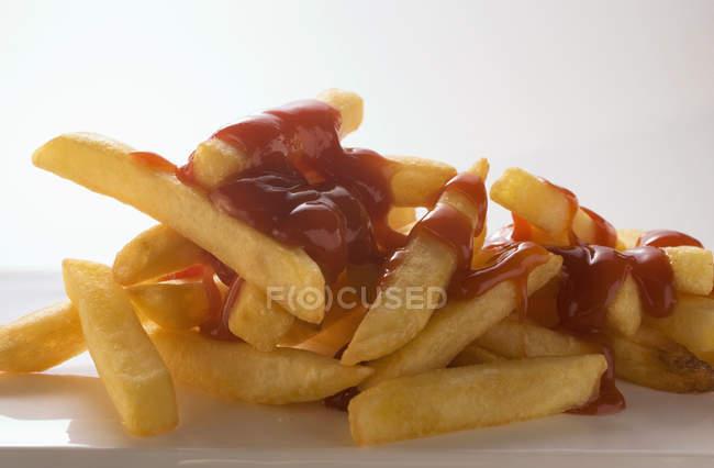 Salsa de tomate en papas fritas de patata - foto de stock