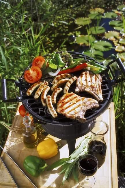 Колбасы и овощи на барбекю — стоковое фото