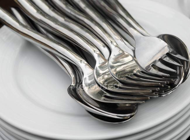 Closeup view of piled plates with spoons and forks — Stock Photo