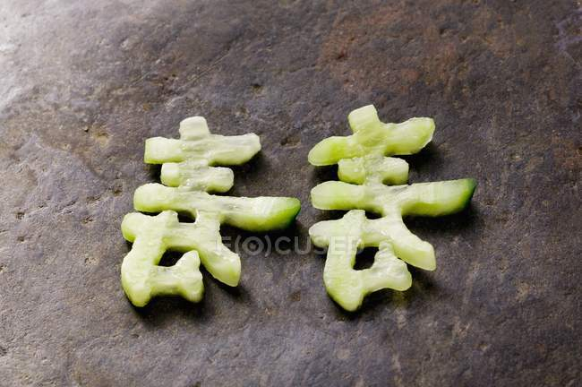 Chinese characters made from cucumber  over wooden surface — Stock Photo
