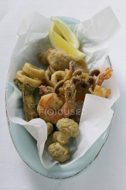 Vista superior de mariscos fritos en papel y tazón de fuente oval - foto de stock