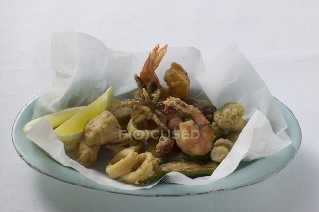 Крупным планом вид deep-fried морепродуктов на бумаге и пластины — стоковое фото
