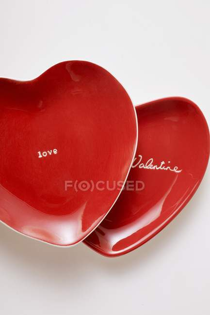 Closeup top view of red heart-shaped plates with the words Be my Valentine and Love — Stock Photo