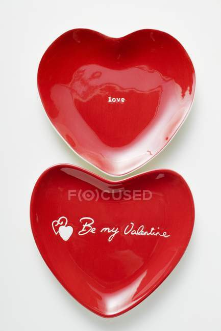 Closeup view of red heart-shaped plates with the words Be my Valentine and Love — Stock Photo