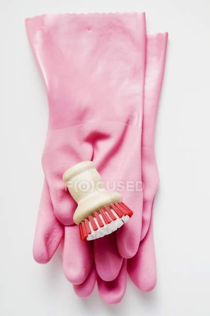 Nahaufnahme von rosa Gummihandschuhen und Pinsel auf weißer Oberfläche — Stockfoto