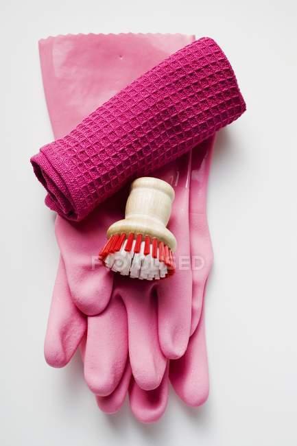 Primo piano vista dall'alto di guanti di gomma rosa, spazzola e asciugamano — Foto stock
