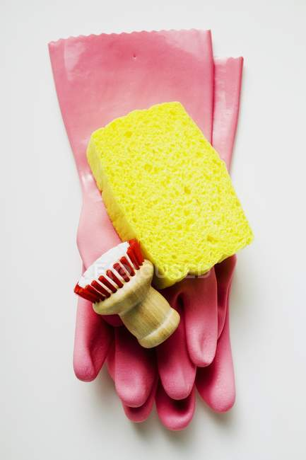 Closeup top view of pink rubber gloves with sponge and brush — Stock Photo