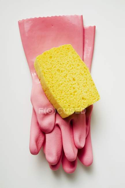 Closeup top view of pink rubber gloves and yellow sponge on white surface — Stock Photo