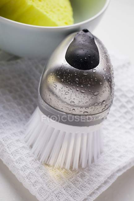 Vue de brosse avec des gouttes d'eau, linge à vaisselle et une éponge dans un bol — Photo de stock
