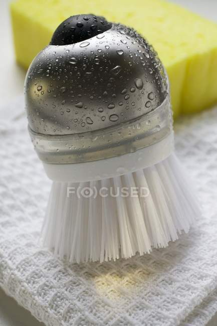 Closeup view of brush with drops of water, tea towel and sponge — Stock Photo