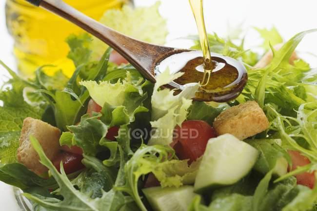 Лить оливкового масла в салат — стоковое фото