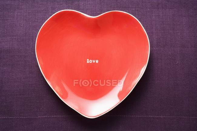Closeup top view of heart-shaped red plate with word Love — Stock Photo
