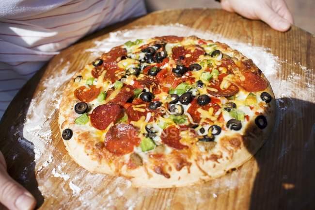 Man holding pepperoni pizza — Stock Photo