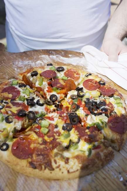 Человек с пиццей пепперони — стоковое фото