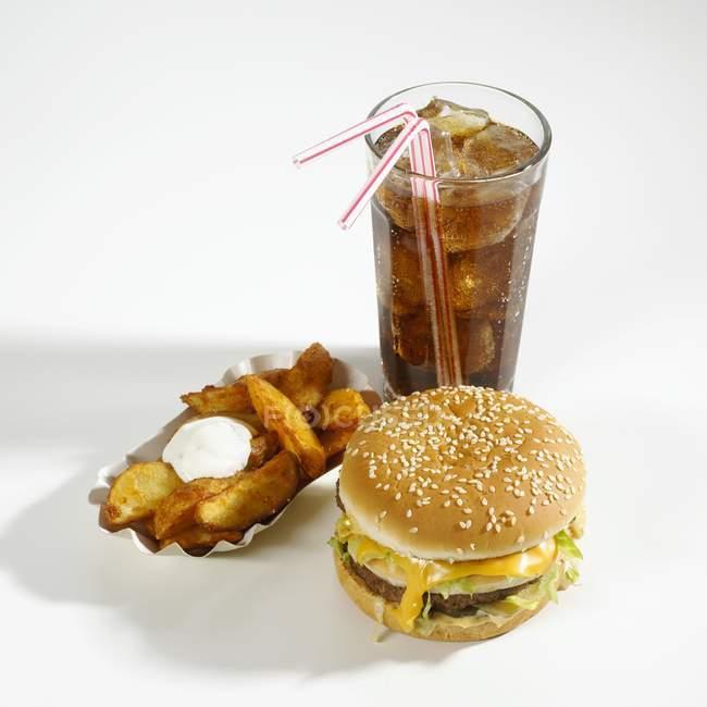 Hambúrguer de queijo, fatias de batata e cola — Fotografia de Stock