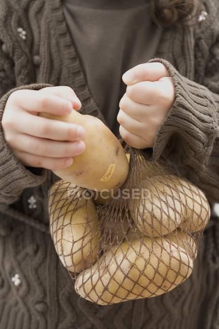 Menina com saco de batatas — Fotografia de Stock