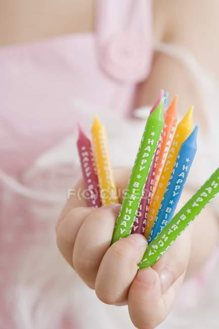 Vue rapprochée de fille tenant des bougies d'anniversaire colorées — Photo de stock