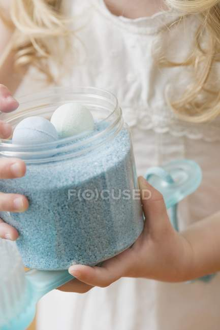 Cropped view of girl holding container of bath products — Stock Photo