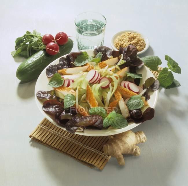 Surimi салат з огірків і зелена цибуля на білий пластини над солом'яний мат — стокове фото
