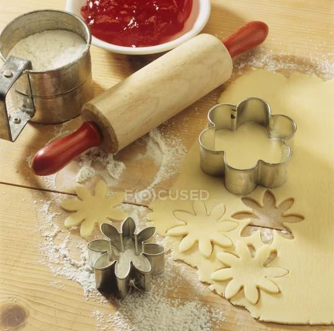 Massa, cortadores de biscoito e rolling pin — Fotografia de Stock