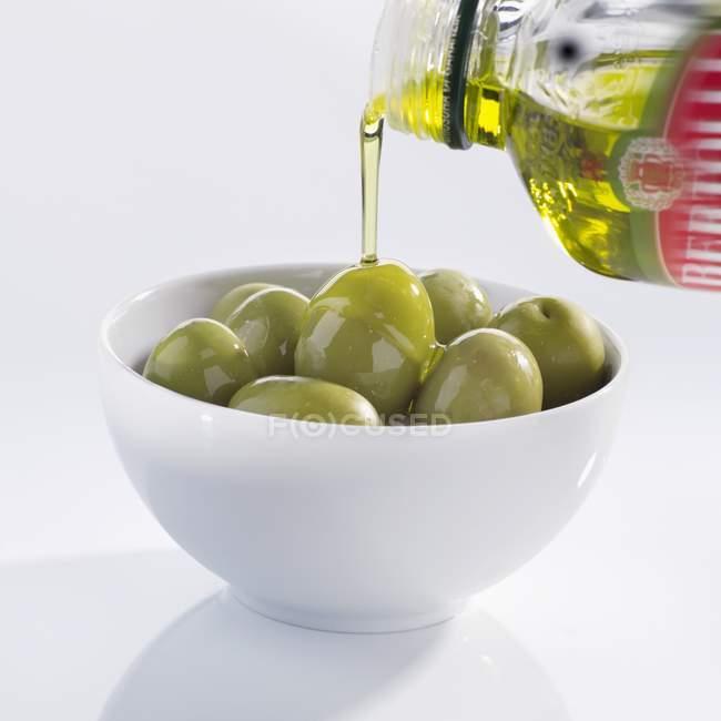 Verser de l'huile d'olive sur les olives — Photo de stock