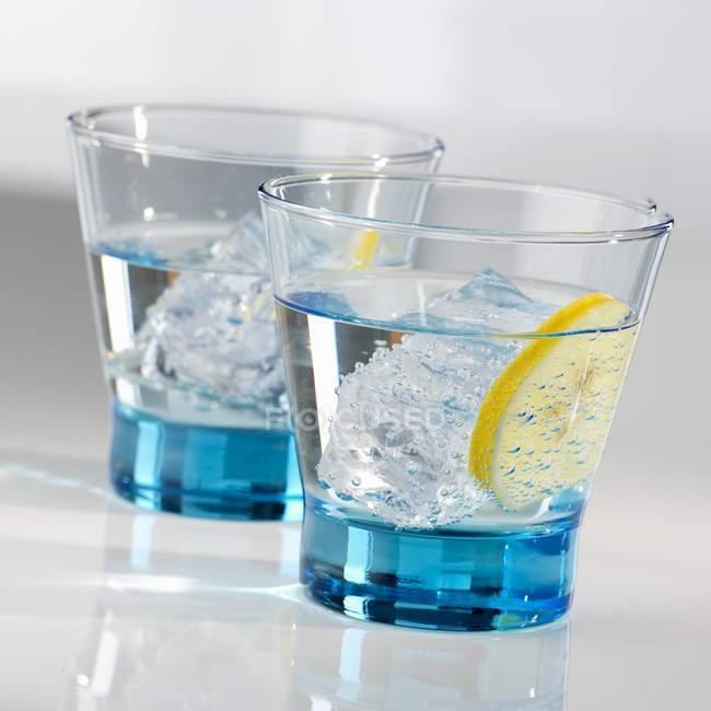 Vista close-up de dois copos de água com cubos de gelo e uma fatia de limão — Fotografia de Stock