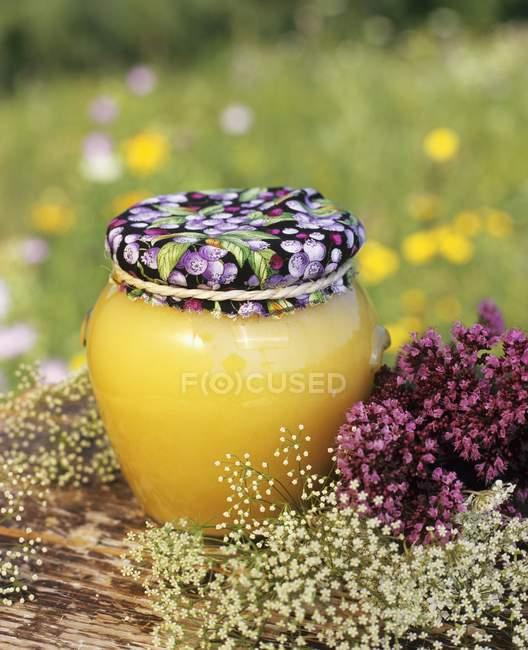 Мед, окруженный цветами — стоковое фото