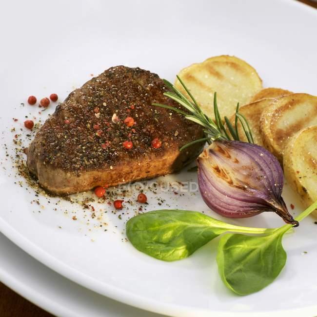 Steak poivre avec pommes de terre et oignon — Photo de stock