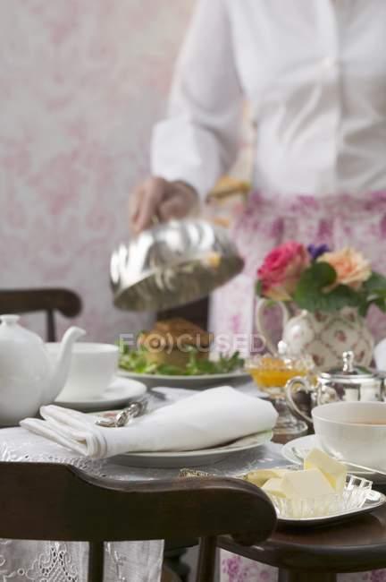 Person öffnen kuppelabdeckung über Gericht am gedeckten Tisch — Stockfoto