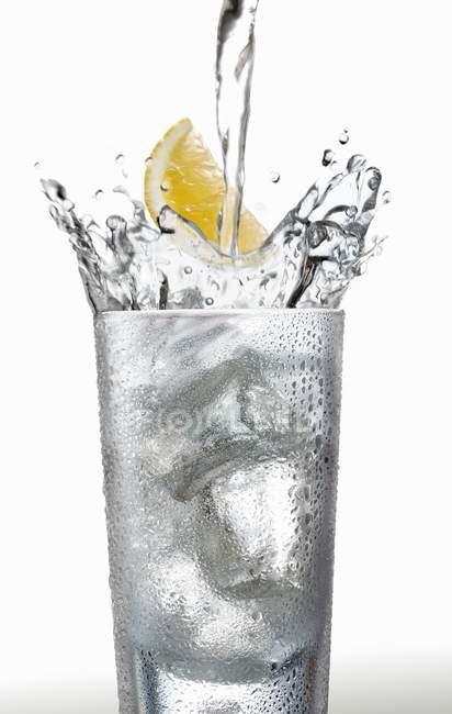 Наливая воду в стекло — стоковое фото