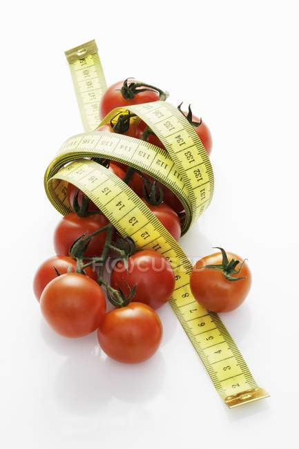 Cocktail tomatoes with tape measure — Stock Photo