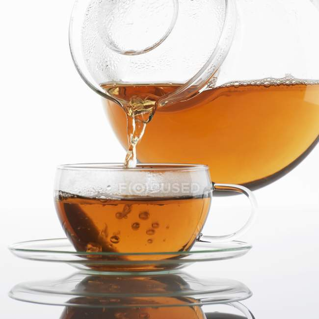Pouring tea into a glass cup — Stock Photo