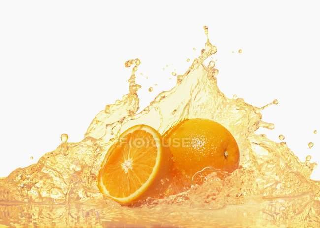 Oranges with splashing orange juice — Stock Photo
