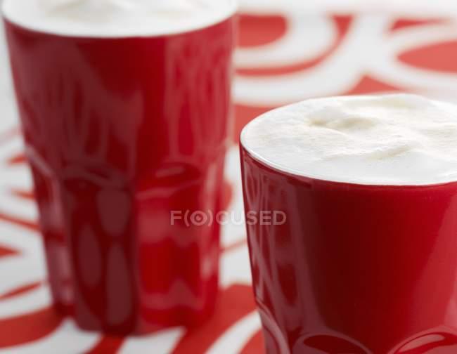Café con espuma de leche en vasos rojos - foto de stock