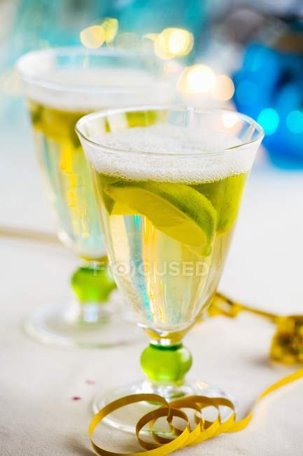 Glasses of sparkling wine with lemon wedges — Stock Photo