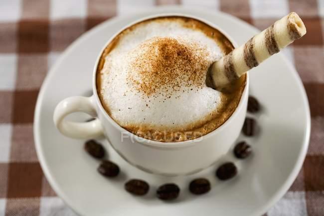 Tazza di cappuccino con rotoli di wafer — Foto stock