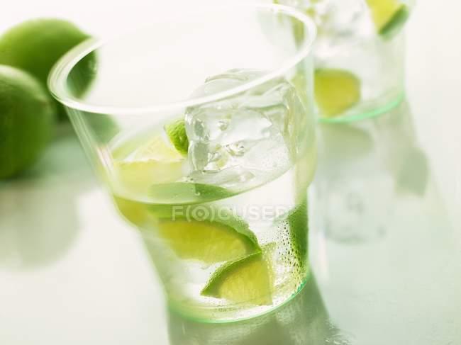 Vista de perto de água mineral com pedaços de limão e cubo de gelo — Fotografia de Stock