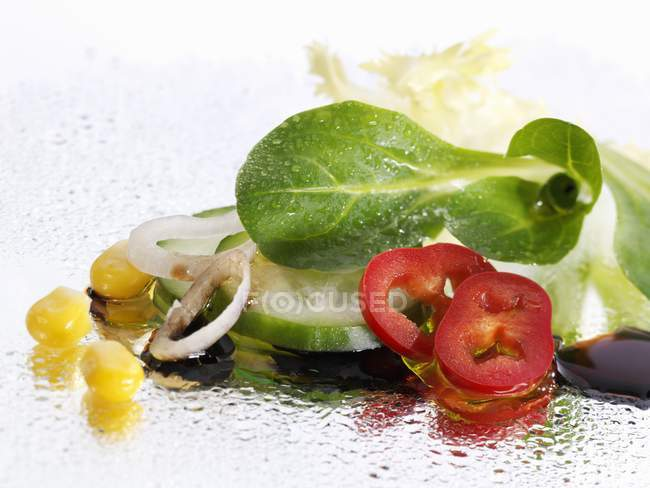 Vegetable salad with balsamic vinegar  over white surface — Stock Photo