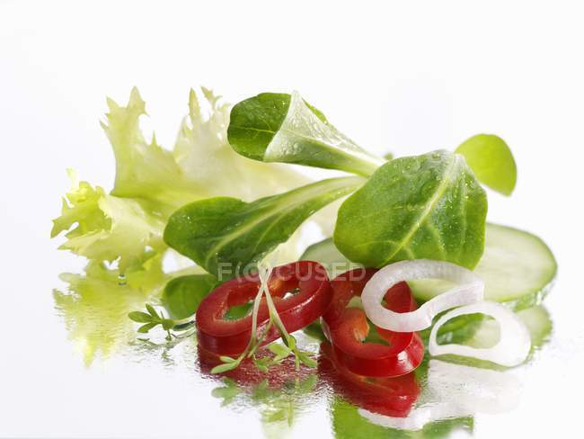 Mixed salad laying on white surface — Stock Photo