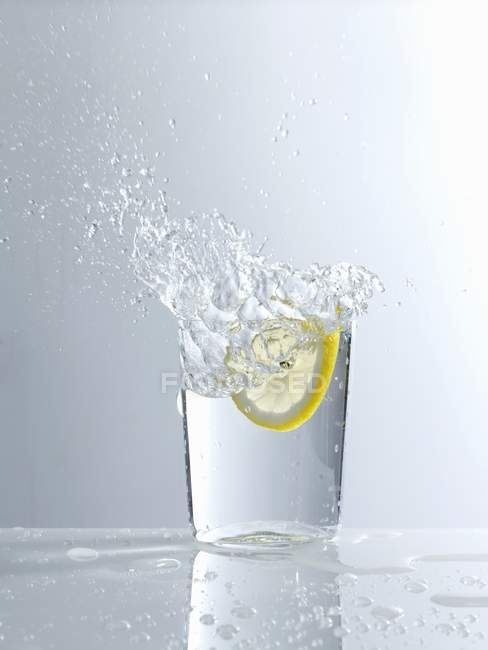 Dropping lemon slice in glass of water — Stock Photo