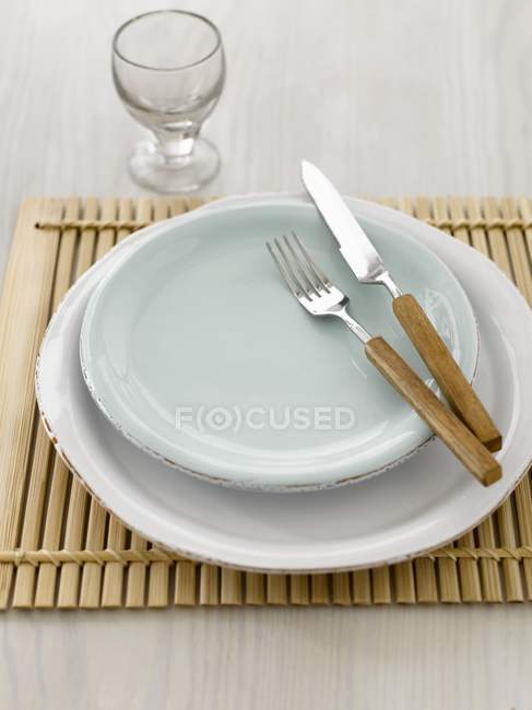 Place setting with knife and fork on wooden mat — Stock Photo