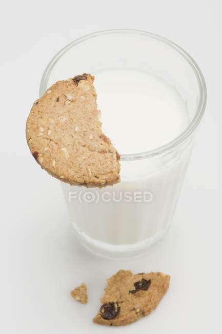 Стакан молока с куском из непросеянной муки печенья — стоковое фото