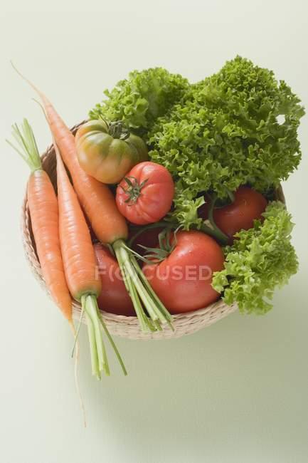 Zanahorias y lechuga en una cesta pequeña - foto de stock