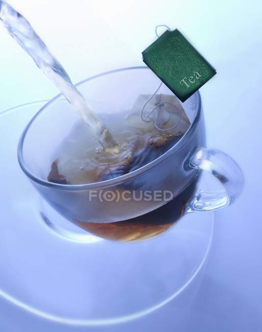 Glass cup with tea bag — Stock Photo
