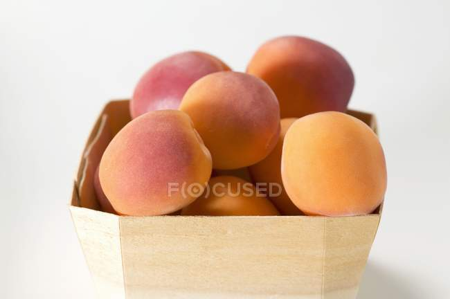 Several apricots in woodchip basket — Stock Photo