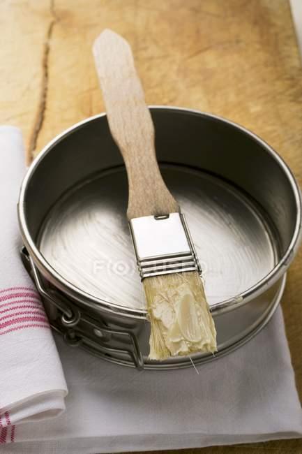 Primo piano vista di pennello con burro sulla teglia — Foto stock